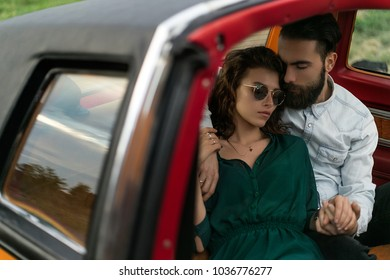 A beautiful couple in love near a vintage car.