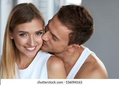 Beautiful Couple In Love. Portrait Of Handsome Man Kissing Happy Smiling Woman With Smooth Soft Silky Face Skin. Romantic Sensual Male And Affectionate Loving Female. Relationships. High Resolution