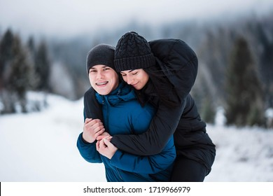 Beautiful couple in love. Portrait of winter background. The guy and the girl have a rest in the winter woods. Husband and wife in the snow. Young couple walking in winter park.