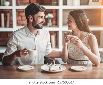Beautiful couple in love is sitting in cafe, drinking coffee and eating cheesecake. Looking softly on each other.