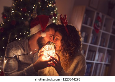 Beautiful couple in love sitting on the living room floor next to a Christmas tree, holding a jar with Christmas lights