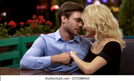 Beautiful couple in love spending their date on open terrace of cozy restaurant