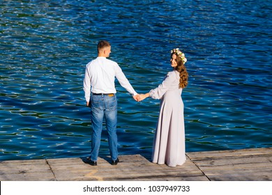 a beautiful couple in love standing on the pier and holding hands and the girl looks back and smiles