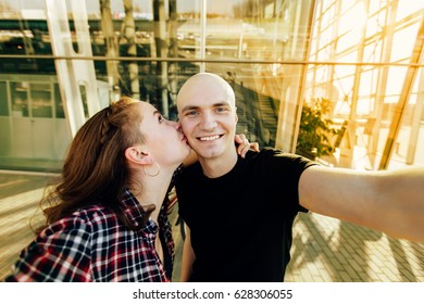 Beautiful couple in love taking selfie photo over urban background. A girlfriend kissing her bald head boyfriend on cheek. A bald head hipster receiving kiss from his girlfriend.