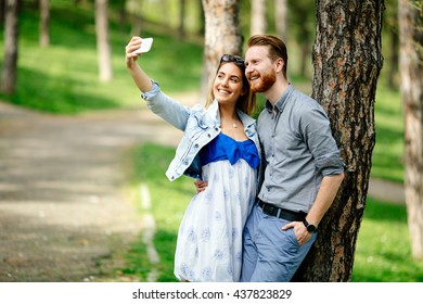 Beautiful couple in love taking slefies outdoors in park