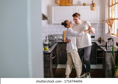 beautiful couple in love, they spend free time together at home, dance in the kitchen. cute couple happy together, have harmonious relationships