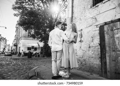 beautiful couple in love walking and gently hugging in sunny green street. stylish hipster groom and blonde bride embracing. romantic moments in summer city street on vacation