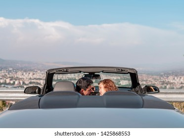 beautiful couple making up in convertible car.