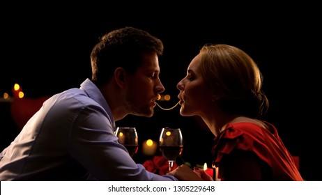 Beautiful couple making spaghetti kiss on romantic date in restaurant, love