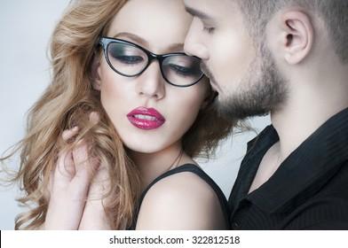 Beautiful couple. Man hugging a blond woman. Woman wearing eyeglasses. Passionate couple in love. Portrait of beautiful woman handsome man. Love. Kiss. Flirt. Lovers.