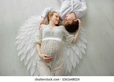 beautiful couple of a man and a pregnant woman in a white lace dress with wings lying on a light floor