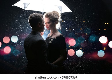 Beautiful couple man with woman  with  white umbrella in flash lights and rain drops