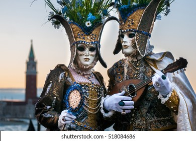 Beautiful couple of masks at St. Mark square during the carnival of Venice.