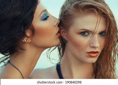 Beautiful couple of models with perfect arty make-up on the beach. Long wet hair and waterproof decorative cosmetics. Close up. American disco (vintage) style. Outdoor fashion shot