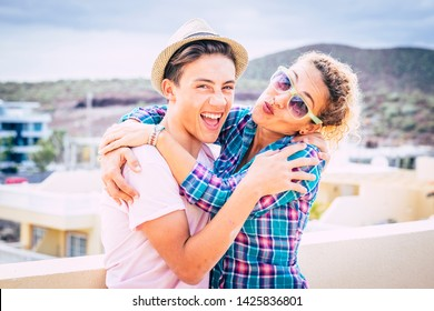 beautiful couple of mum and son together hugged in the terrace of the home having fun and laughing - woman with sunglasses and teenager with a relationship - guy with a hat hapy and funny