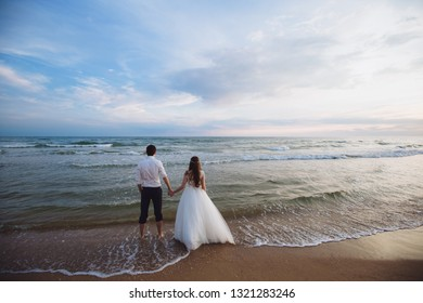 A beautiful couple of newlyweds, the bride and groom walking on the beach. Gorgeous sunset and sky. Wedding dresses, a white luxury dress for a girl. Family concept, honeymoon