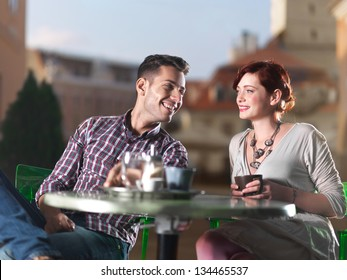 beautiful couple on coffee on the terrace in the town square at sunset