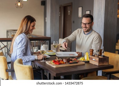 Beautiful couple on a date at restaurant, eating lunch and having fun
