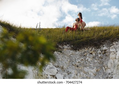Beautiful couple on the mountain. A guy and a girl are kissing against the sky