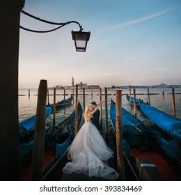 Beautiful couple on the pier among gondolas