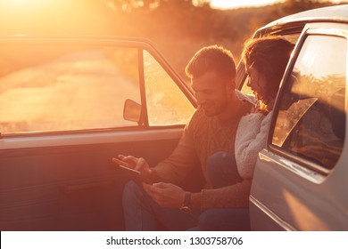 Beautiful couple on road trip, they are taking a break from driving and looking for direction on tablet.