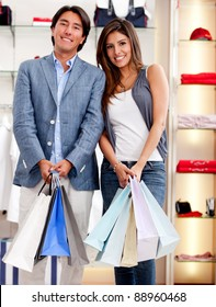 Beautiful couple out for shopping holding bags and smiling