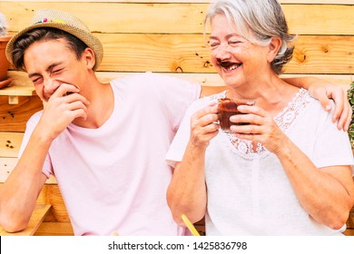 beautiful couple of people having fun and joking together with a grandma drinking hot chocolate and with some chocolate on her mouth - caucasian and young teenager laughing and hugging she -  dirty