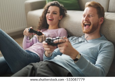 Beautiful couple playing video games on console having fun