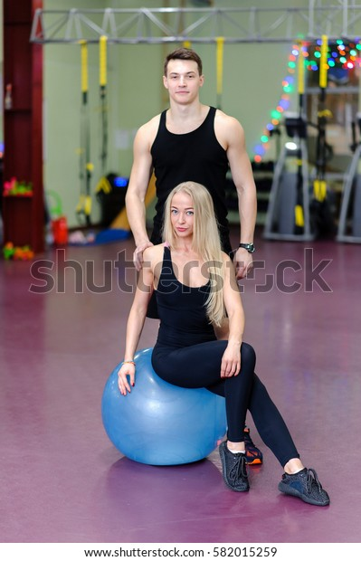 Beautiful couple posing on a fitball at the gym