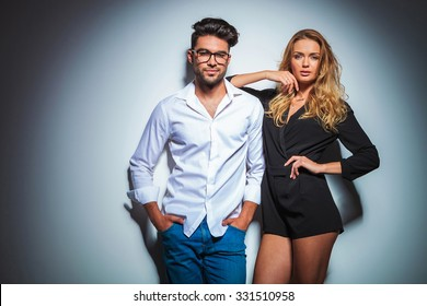beautiful couple posing in studio he with hands in pockets while she rest her arm on his shoulder