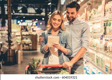 Beautiful couple is reading lists of goods and smiling while doing shopping at the supermarket