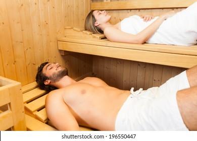Beautiful couple relaxing while taking a sauna