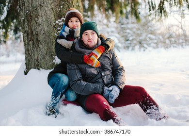 Beautiful couple relaxing in the winter forest is sitting under a tree