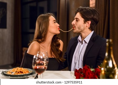 Beautiful couple in a restaurant eating spaghetti together.