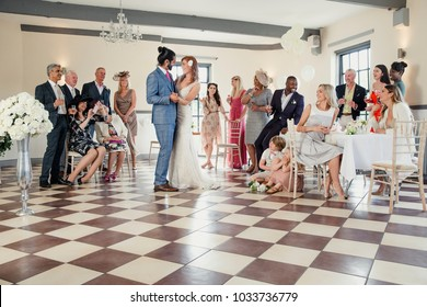 Beautiful couple are sharing their first dance on their wedding day. All of their guests are sitting around the dancefloor watching them.
