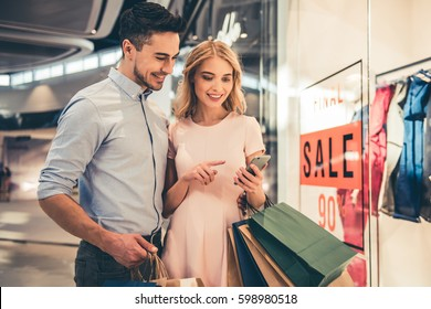 Beautiful couple with shopping bags is using a smartphone and smiling while doing shopping in the mall