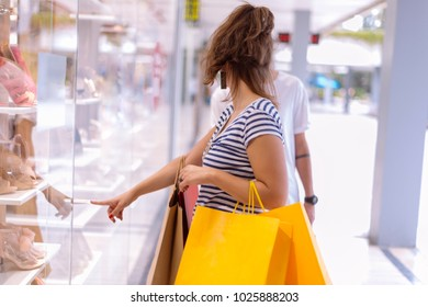 Beautiful couple shopping in the city walking and holding shopping bags. Shopping concept