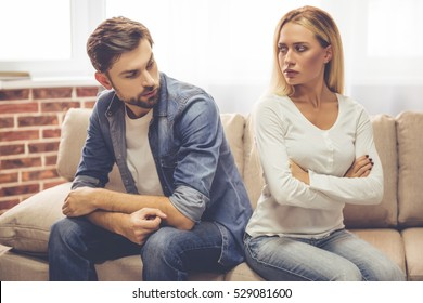 Beautiful couple is sitting back to back on the couch and looking offended at each other while having a quarrel