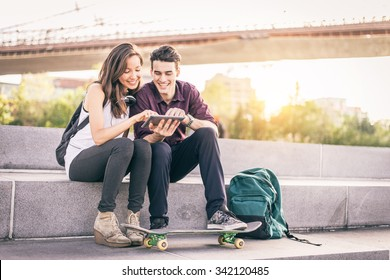 Beautiful couple sitting on a bench outdoors and looking at tablet - Lovers having fun with new technology and shopping online