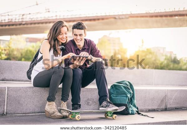 Schönes Ehepaar, das auf einer Bank im Freien sitzt und Tablet anschaut - Liebhaber der neuen Technologie und des Online-Shopping
