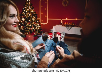 Beautiful couple sitting on the couch holding glass of wine in a decorated festive interior with a Christmas tree.