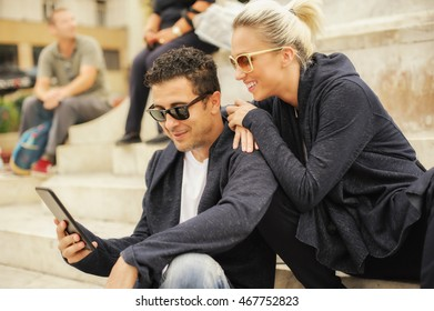 Beautiful couple sitting on steps of monument and looking at tablet
