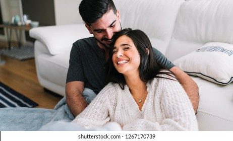 Beautiful couple is smiling and hugging while spending time together in bed at home.