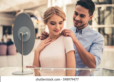 Beautiful couple is smiling while choosing jewelry in the shopping mall
