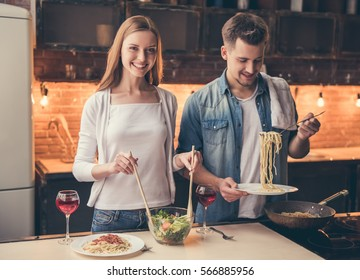 Beautiful couple is smiling while cooking together in the kitchen
