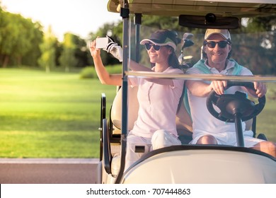 Beautiful couple is smiling while driving a golf cart, girl is taking photos using a smart phone