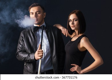 Beautiful couple smoking hookah. Producing the smoke from his mouth. Business style clothing. The pleasure of smoking. Love.