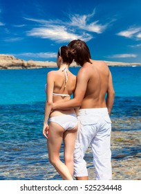A beautiful couple standing near blue the sea
