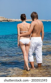 A beautiful couple is standing near the sea