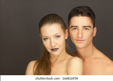 beautiful couple in studio portrait front view pose for the camera, the man behind